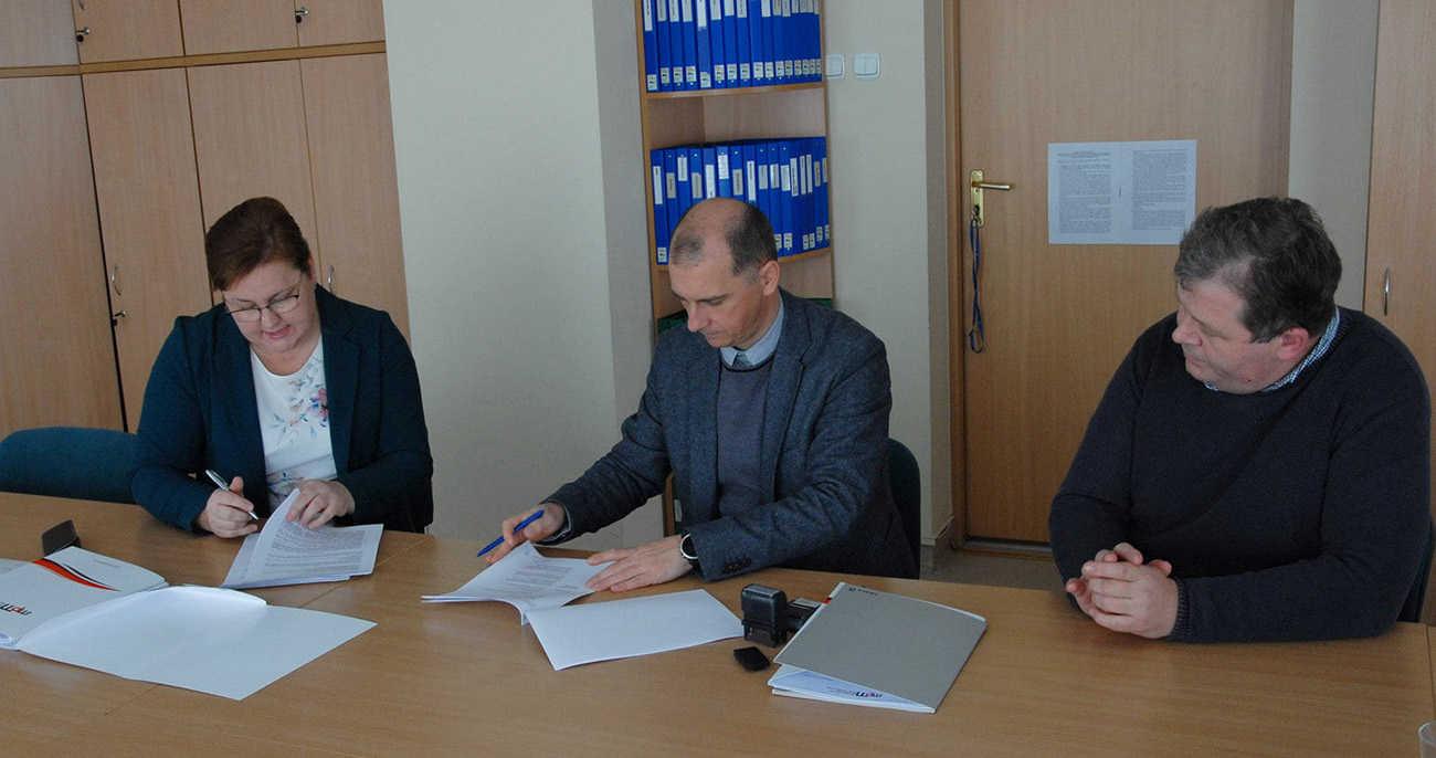 Trzy osoby podpisujące umowę w tym jedna kobieta pierwsza z lewej